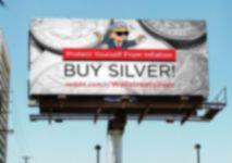 Panneau d'affichage montrant le bonhomme wall street silver de reddit avec des pièces d'argent en arrière-plan et les phrases protégez-vous de l'inflation achetez de l'argent reddit.com/r/Wallstreetsilver