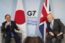 UK Prime Minister Boris Johnson and Japanese Prime Minister Yoshihide Suga attending a meeting on the sidelines of the G7 summit in Cornwall with the Japanese and British flags standing in the background.