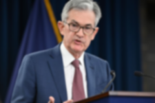fed chair jerome powell addressing a meeting in a blue suit
