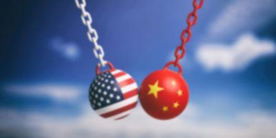 Deux boulets avec chaîne et des drapeaux des États-Unis et de la Chine se frappant l'un contre l'autre pour représenter les tensions économiques et géopolitiques qui pourraient influencer la stabilité des marchés boursiers