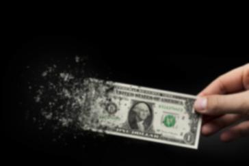 Un billet d'un dollar dans la main d'un homme sur fond noir, signalant l'inflation, la faiblesse du dollar et le fait que les fonds russes se débarrassent de tous leurs actifs en dollars américains.