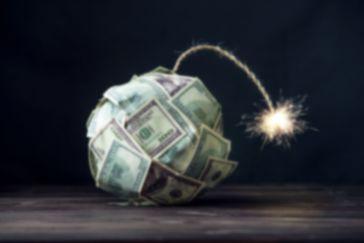 Une bombe représentant l'inflation, constituée de billets de 100 dollars US, en train de fumer et sur le point d'exploser sur l'économie mondiale.