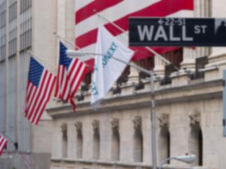 Nahaufnahme eines Wall-Street-Schildes in New York und des Börsengebäudes im Hintergrund mit US-Flaggen