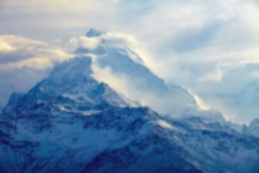 a picture showing blue mountains surrounded by fog and clouds