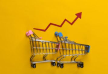 Steigende Lebensmittelpreise, ein roter Pfeil steigt über zwei Einkaufswagen auf goldenem Hintergrund