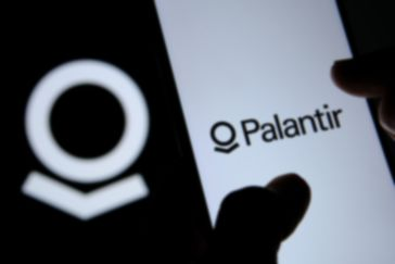 us tech giant palantir banner on the phone screen with a black and white palantir logo in the background
