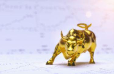 Ein Goldbulle mit Aktiencharts im Hintergrund, die einen wachsenden Aufwärtstrend bei Gold symbolisieren