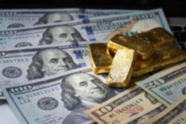 Dollarscheine mit rohen Goldbarren obenauf symbolisieren das exzessive Gelddrucken, das eine wichtige Rolle für den Goldpreis spielt.