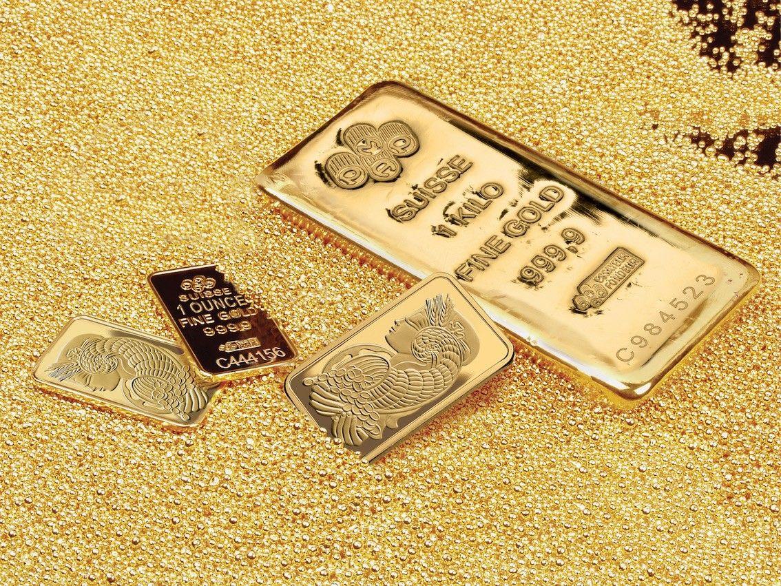 geprägte Barren und gegossene Goldbarren, die in einem Becken mit Goldkügelchen liegen